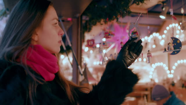 woman looking at christmas ornaments at christmas market stall - market stall stock videos & royalty-free footage