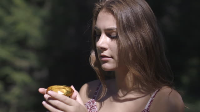 woman looking at crystal in countryside - gem stock videos and b-roll footage