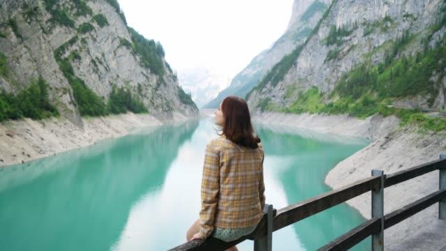 vidéos et rushes de femme regardant le barrage dans les alpes suisses - barrage