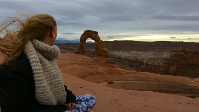 woman looking at delicate arch, arches national park - windswept stock videos & royalty-free footage