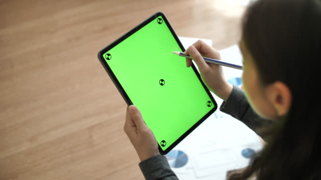 woman looking at digital tablet and using digital pen with green screen - digitized pen stock videos & royalty-free footage