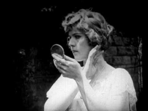 vidéos et rushes de b/w 1925 portrait woman looking at face in compact + looking at camera / newsreel - maquillage