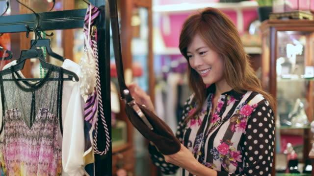 vídeos de stock, filmes e b-roll de cu woman looking at handbag in shop - antiquário loja