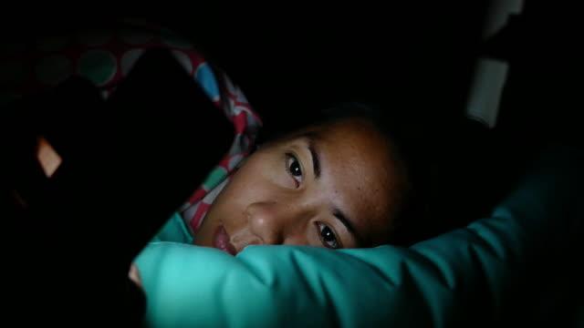 stockvideo's en b-roll-footage met vrouw kijken naar haar mobiele telefoon in de slaapkamer - vlak naast