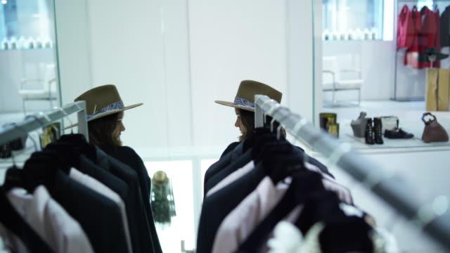 stockvideo's en b-roll-footage met vrouw kijken naar zichzelf in een spiegel proberen op kleding - paskamer