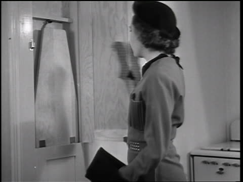 b/w 1935 woman looking at ironing board in closet in kitchen of model home / educational - bügelbrett stock-videos und b-roll-filmmaterial
