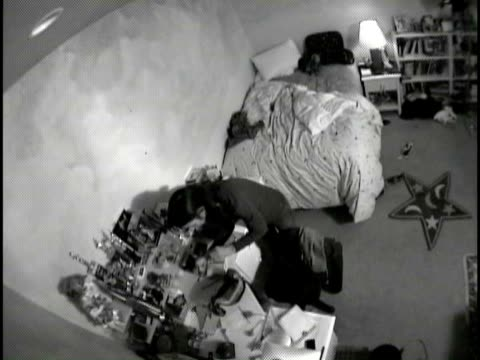 B/W POV HA WS Woman looking at items on desk and searching through purse in child's bedroom, then man enters, they search desk together and then leave / White Plains, New York, USA