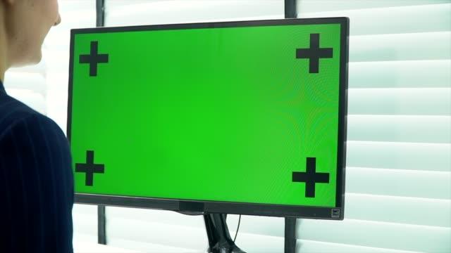 frau schaut laptop mit grünem bildschirm an - über die schulter stock-videos und b-roll-filmmaterial