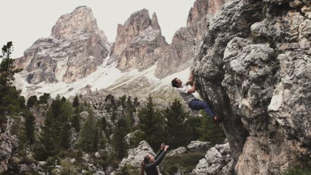 stockvideo's en b-roll-footage met vrouw die man bekijkt die berg beklimt - free climbing