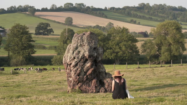a woman looking at megalith at the stanton drew stone circle - obelisk stock videos & royalty-free footage