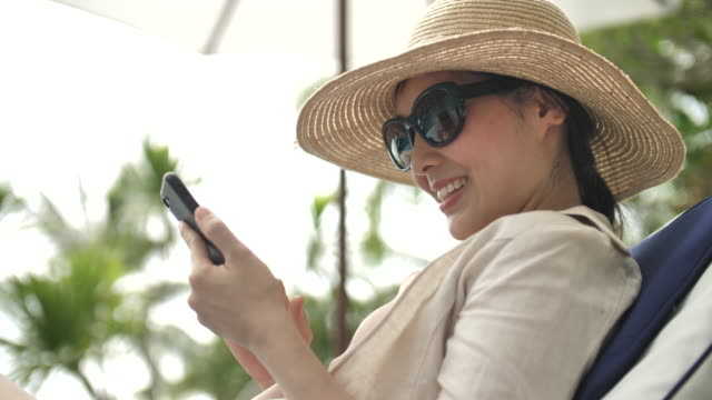 woman looking at mobile phone in hammock at the beach - sun lounger stock videos & royalty-free footage