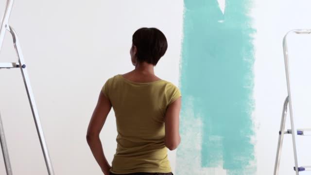 stockvideo's en b-roll-footage met woman looking at paint on wall - keukentrap