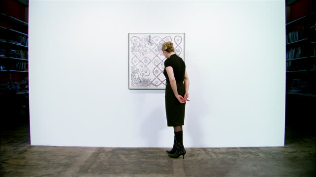 Woman looking at painting hanging on wall in art gallery