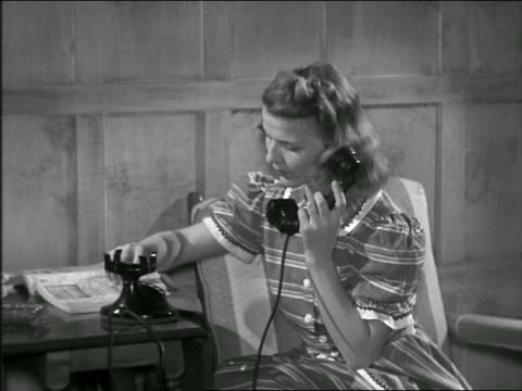 vídeos y material grabado en eventos de stock de b/w 1948/49 woman looking at phone book + dialing on rotary phone at home / smiles + starts talking - directorio