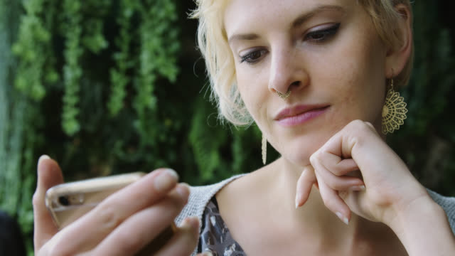 woman looking at phone - nose piercing stock videos & royalty-free footage