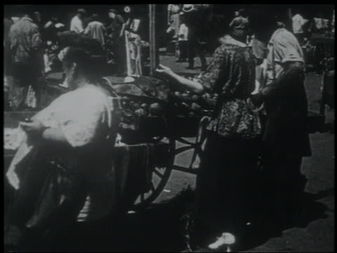 vídeos de stock e filmes b-roll de b/w 1903 newsreel rear view woman looking at produce on pushcart on street in lower east side / nyc - 1903