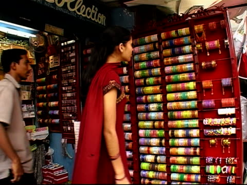 stockvideo's en b-roll-footage met woman looking at racks of bangles at outdoor market stall / making selection and pointing to bangles / merchant removing rack off shelf / bangalore, karnataka, india - mid volwassen mannen