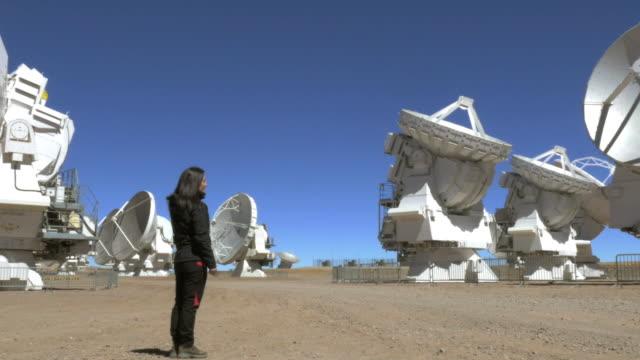 woman looking at radio telescope array - atacama large millimeter array stock videos and b-roll footage