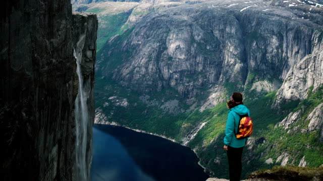 woman looking at scenic view of lysefjorden from kjerag mountain - norway stock videos & royalty-free footage