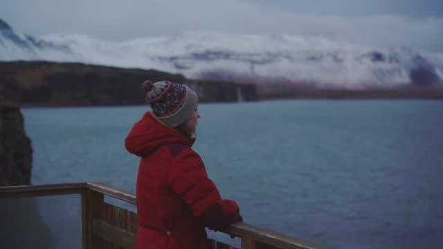 vidéos et rushes de femme regardant la vue panoramique sur la mer en islande - manteau et blouson d'hiver