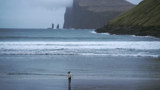 vídeos y material grabado en eventos de stock de mujer mirando a la vista panorámica de la costa en islas faroe - jersey de cuello alto