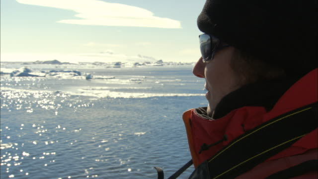 cu, woman looking at sea with ice floes from ship, antarctica - climate research stock videos & royalty-free footage