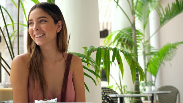 MS Woman looking at smartphone while drinking iced coffee in outdoor cafe