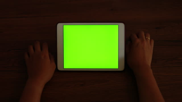 vídeos de stock e filmes b-roll de woman looking at tablet with green screen - leisure equipment