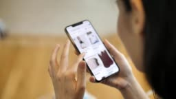 Woman looking at the goods in the online clothing store, Smart phone online shopping, Slow motion.