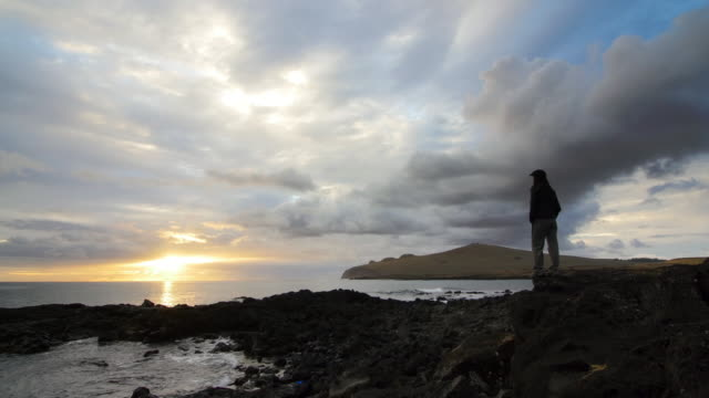 woman looking at the sea and sunrise in the coast - remote location video stock e b–roll