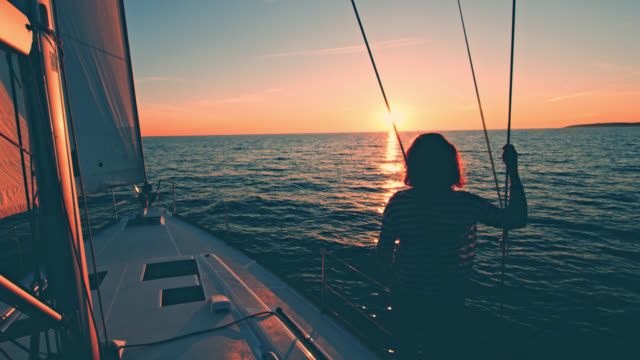 ws woman looking at the sunset on a sailing sailboat - sailing stock videos and b-roll footage