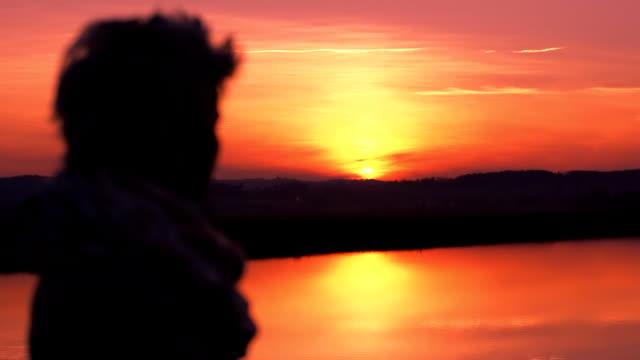 HD : 夕日を見ている女性、
