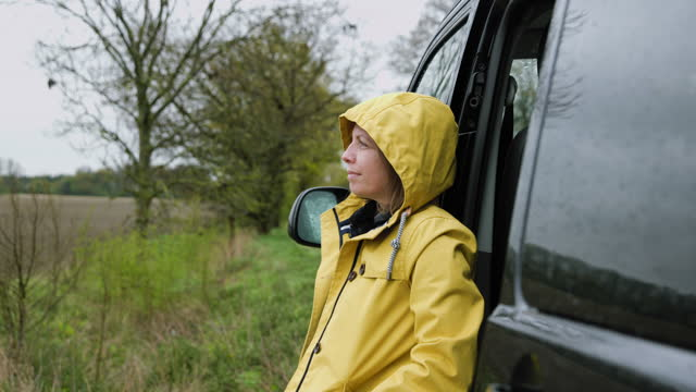 woman looking at the view by her campervan in wet weather - hope stock videos & royalty-free footage