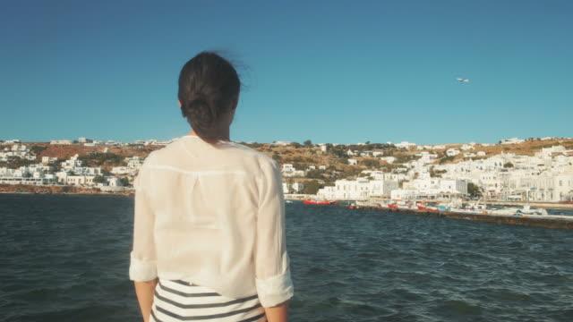 stockvideo's en b-roll-footage met vrouw kijken naar de weergave van mikonos, griekenland. - cross processen