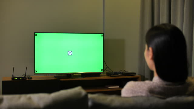 woman looking at tv with green screen at night - guardare la tv video stock e b–roll