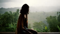 Woman looking at  view of jungles under the rain  in Bali