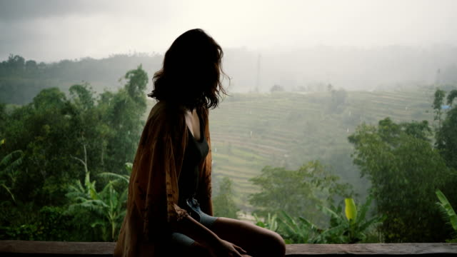 woman looking at  view of jungles under the rain  in bali - clima tropicale video stock e b–roll
