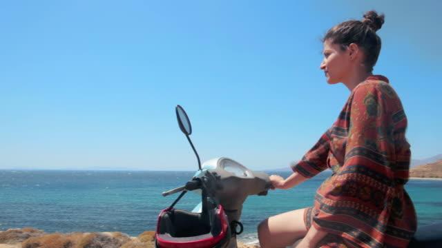 モーター スクーターに座って景色を探している女性 - 見つめる点の映像素材/bロール
