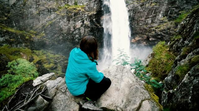 Woman looking at Voringfossen Waterfall in mountains in Norway