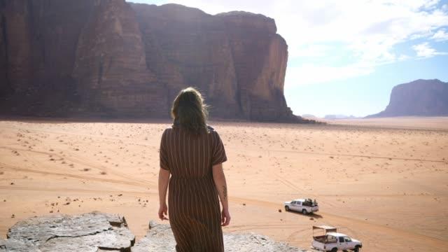 vidéos et rushes de femme regardant le désert de wadi rum - paysage aride