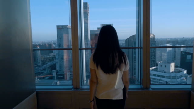 woman looking cityscape in office - window stock videos & royalty-free footage