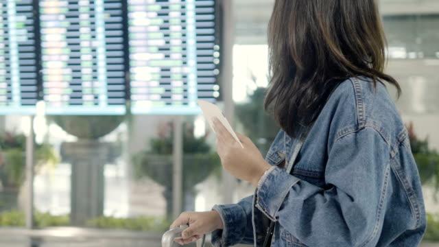 Frau, die Abfahrtstafel am Flughafen