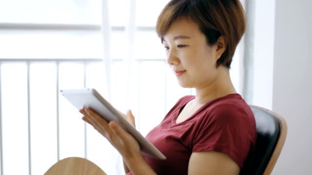 woman looking digital tablet on veranda - chinese ethnicity stock videos & royalty-free footage