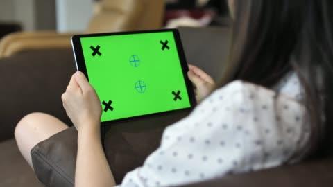 女性看數位片與綠色螢幕, 水準 - 沙發 個影片檔及 b 捲影像