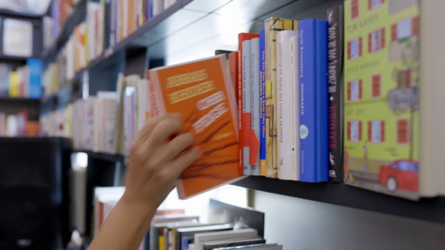 woman looking for books at store - book shop stock videos & royalty-free footage