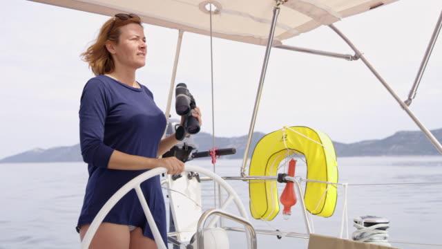 stockvideo's en b-roll-footage met ws vrouw op zoek naar richting tijdens het zeilen - crew