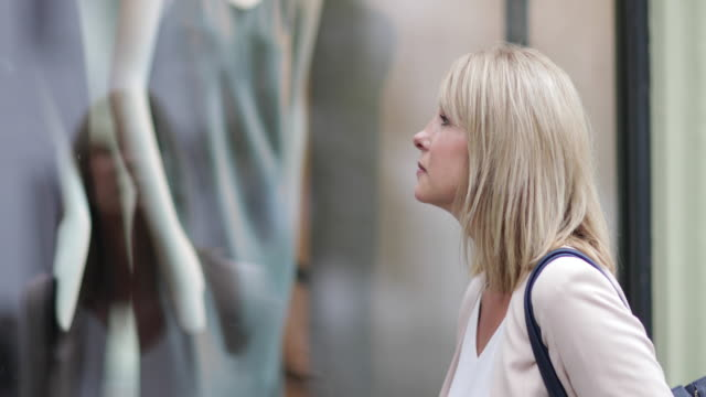 woman looking in a store window - window display stock videos and b-roll footage