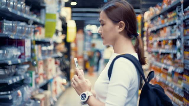 vidéos et rushes de femme regardant en supermarché - photographing