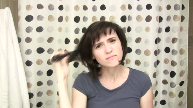 stockvideo's en b-roll-footage met woman looking into camera brushing hair - haar borstelen