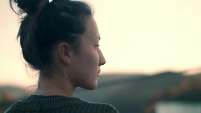 woman looking into distance at sunrise - serenità video stock e b–roll